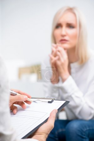 Photo for Tell me the truth. Selective focus of folder in hands of professional psychologist holding it and interrogating patient during psychological therapy session - Royalty Free Image