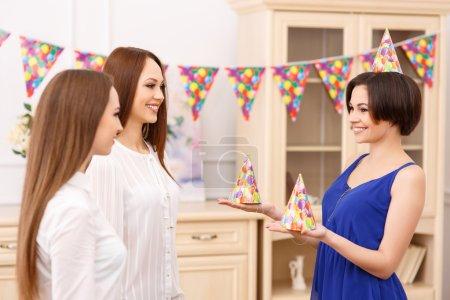 Photo pour La fête commence. Jeune fille d'anniversaire attrayante offre à ses amis chapeaux de fête spéciaux - image libre de droit