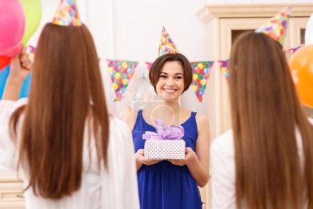Photo pour Obtenir des cadeaux. Attrayant jeune fille sourit vivement tout en tenant son paquet d'anniversaire - image libre de droit
