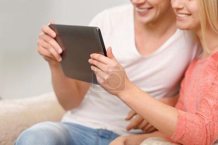 Photo pour Joli couple. Jeune couple semble heureux en regardant quelque chose sur la tablette - image libre de droit