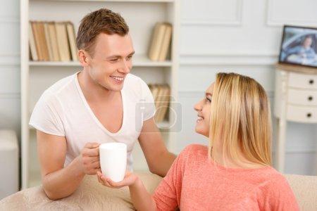 Photo pour Joyeux couple. Jeune couple semble heureux tout en étant assis sur le canapé et boire du thé - image libre de droit