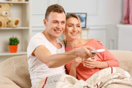 Photo pour À la télé. Jeune couple boit du thé et utilise la télécommande pour changer de chaîne sur la télévision - image libre de droit