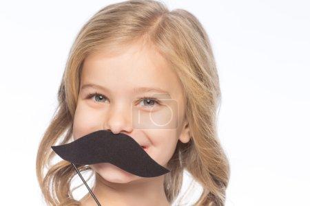 Photo pour Une fille avec une moustache en papier. Petite fille sourit tout en maintenant moustache en papier décoratif - image libre de droit