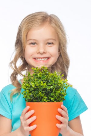 Photo pour Fille avec des fleurs. Petite fille sourit vivement tout en tenant la plante verte dans le pot de fleurs - image libre de droit