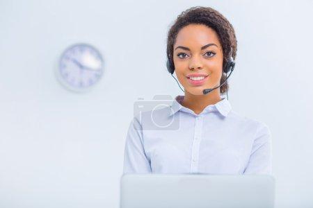 Foto de Rodeado de dispositivos. Trabajadora de oficina joven está sentada en el escritorio y haciendo sus deberes - Imagen libre de derechos