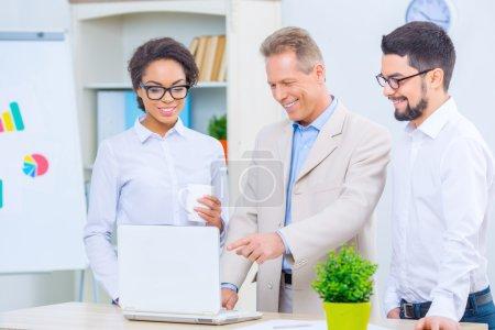 Foto de En la oficina. Tres colegas de aspecto agradable están en la sala de conferencias y discutiendo un proyecto - Imagen libre de derechos