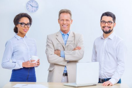 Foto de Gente exitosa. Tres trabajadores de oficina sonríen agradablemente mientras posan en la cámara - Imagen libre de derechos