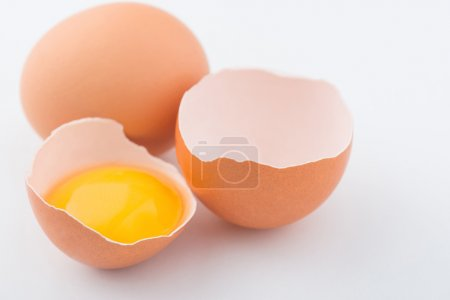 Chicken eggs are on white surface.