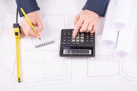 Photo pour Des calculs exacts. Les mains masculines utilisant la calculatrice et les résultats d'écriture dans un petit bloc-notes - image libre de droit