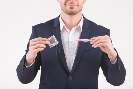 Man upholding condom and pregnancy test.
