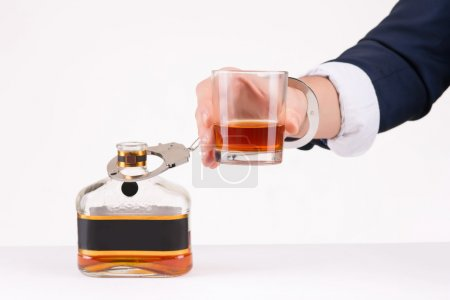 Photo for Drinking habit. Male hand chained to hard alcoholic beverage - Royalty Free Image