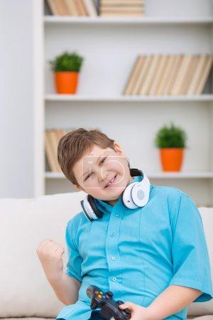 Photo pour Un score gagnant. Joufflu garçon souriant dans les écouteurs est souriant et acclamant tout en tenant un joystick - image libre de droit