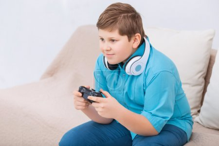 Chubby kid is playing video games.