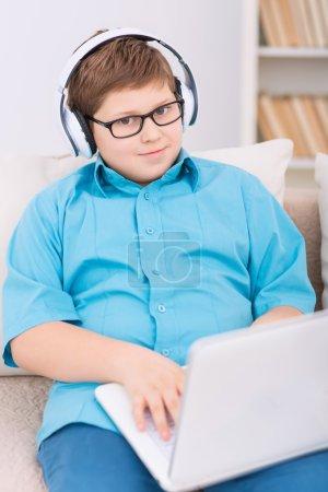 Photo pour Enfant avec ordinateur portable. Chubby garçon en lunettes et écouteurs est assis sur le canapé tout en tenant son ordinateur portable - image libre de droit