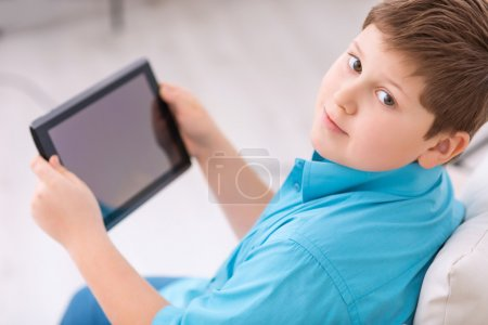 Photo pour Enfant et tablette. Chubby garçon se repose sur le canapé et tenant sa tablette portable - image libre de droit