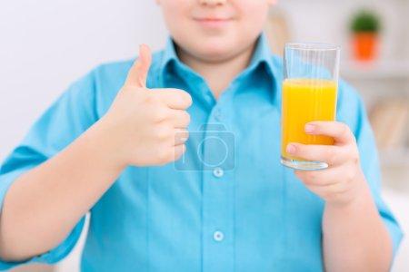Photo pour Une boisson saine. Chubby boy tient un verre de jus d'orange et montre pouces vers le haut - image libre de droit