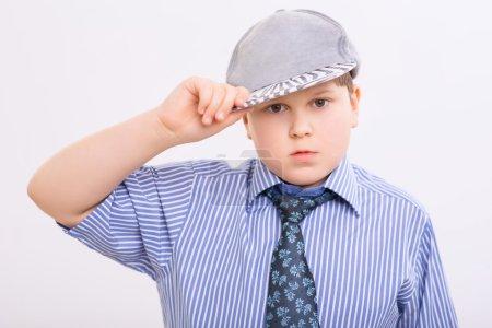 Photo pour Enfant en casquette. Chubby garçon est debout et ajuster sa casquette fantaisie - image libre de droit