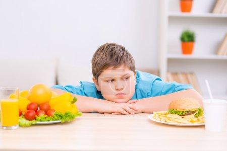 Chubby boy está buscando comida chatarra plato .