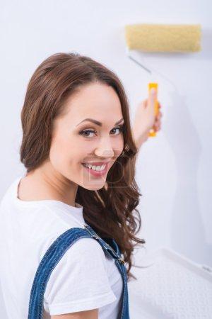Photo pour Répandre une peinture. Jeune fille attrayante dans le rôle masculin est souriant et haletant un mur - image libre de droit