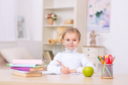 Little girl is sitting at the desk