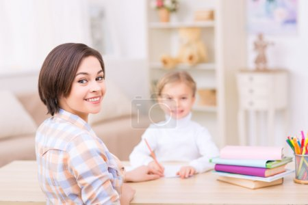 Young mom and her daughter at the desk.