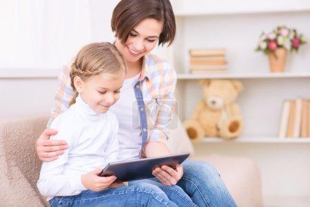 Photo pour Je regarde des dessins animés. Petite fille et sa mère sont assis sur le canapé et regardent quelque chose sur tablette portable - image libre de droit