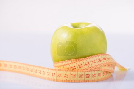 Apple and measuring tape on the surface.