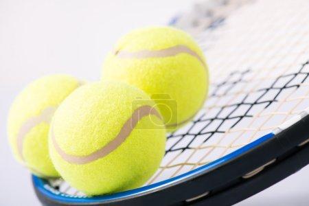 Photo pour Équipement de tennis. Trois balles de tennis jaunes et une raquette qui les détient - image libre de droit