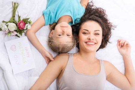 Photo pour Jolies filles. Maman et sa fille sourient pendant qu'elles sont couchées au lit et ensemble avec des fleurs et une carte de vœux - image libre de droit