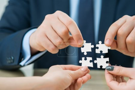 Office workers holding puzzles