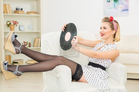 Young appealing woman with vinyl record.