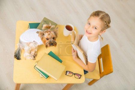 Foto de Tiempo de estudio. La niña está sentada en el escritorio cargada de libros y su perro está sentado a su lado. - Imagen libre de derechos