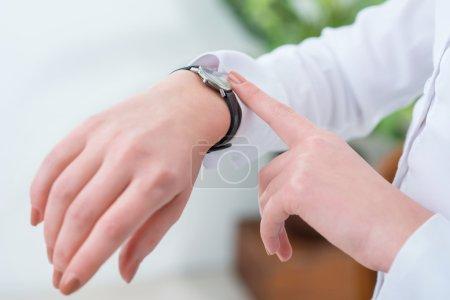 Photo pour Suivez votre horaire. Gros plan de la main de belle femme qui la touche tout en regardant sa montre-bracelet - image libre de droit