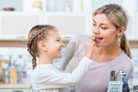 Photo pour C'est pour toi. Joyeux mignon petite fille tenant tranche de concombre et le donnant à sa mère tout en cuisinant ensemble dans la cuisine - image libre de droit