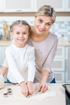 Mother and her little daughter cooking