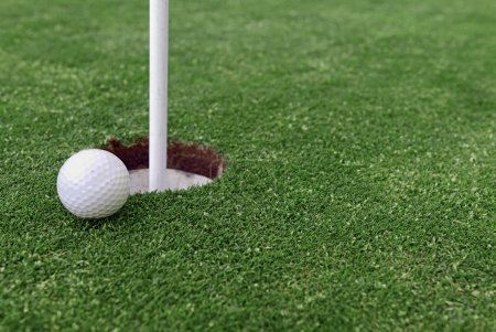 Golf ball and Flagstick of  Mancured grass of putting green