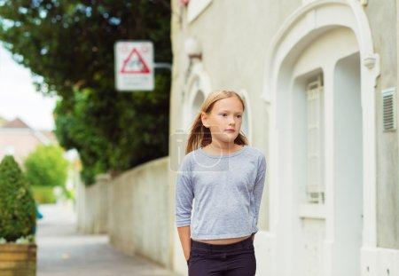 Photo pour Mode portrait de jolie petite fille de 7-8 ans, marchant dans la rue, porte haut gris, aux tons d'image - image libre de droit