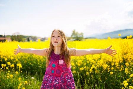 Portrait en plein air d'une jolie petite fille jouant avec des fleurs dans une campagne, bras grands ouverts