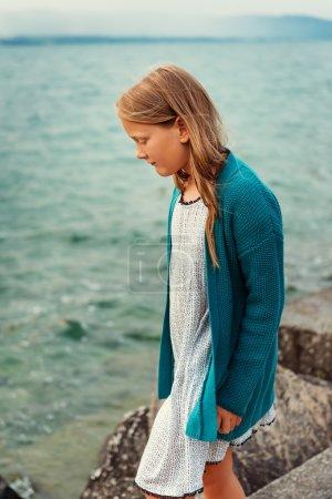 Photo pour Adorable petite fille de 8-9 ans jouant au bord du lac, portant la robe blanche et une veste bleue - image libre de droit
