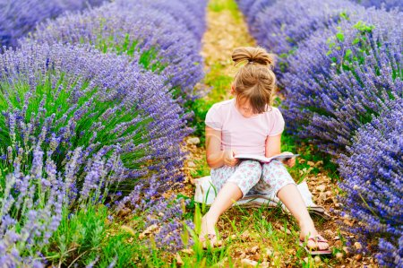Adorable little girl reading a book in a lavender field on a nice sunny evening