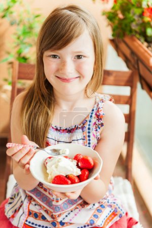 Cute little girl eating strawberry with ice cream on a balcony on a nice sunny day