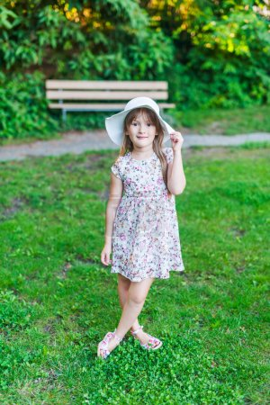 Adorable little girl in a white dress with flowers and hat in a park on a nice day