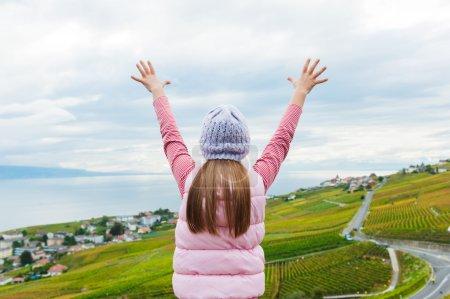 Photo pour Kid fille se tenir entre les vignobles de Lavaux en regardant la vue avec les bras ouverts - image libre de droit