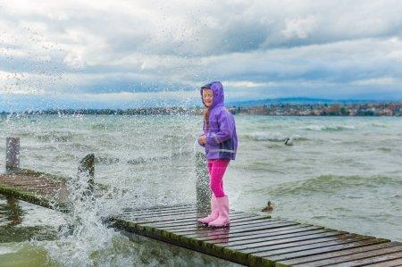 Bambina sveglia che gioca allaperto vicino al lago su un freddo