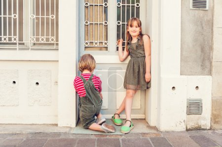 Cute kids playing outdoors, wearing khaki color clothes