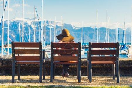 Photo pour Petite fille assise sur le banc et en regardant la vue imprenable, portant chapeau à large bord, retour de vue - image libre de droit