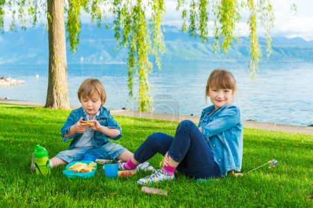 Two cute kids, little girl and her brother, having a picnic outdoors by the lake