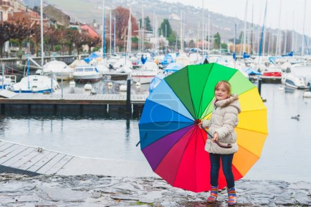 Photo for Outdoor portrait of a cute little girl of 6 years old with big colorful umbrella, playing by the lake on a cold rainy day, wearing warm white coat and rainbow boots - Royalty Free Image