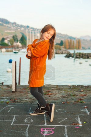 Foto de Portrait of a cute little girl playing outdoors, wearing bright big orange mother's pullover - Imagen libre de derechos