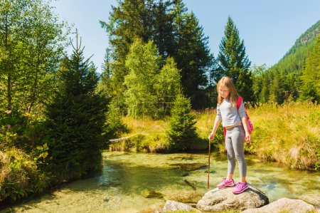 Cute little girl of 7-8 years old hiking in swiss Alps, resting by the river, wearing sport clothes, trainers and backpack